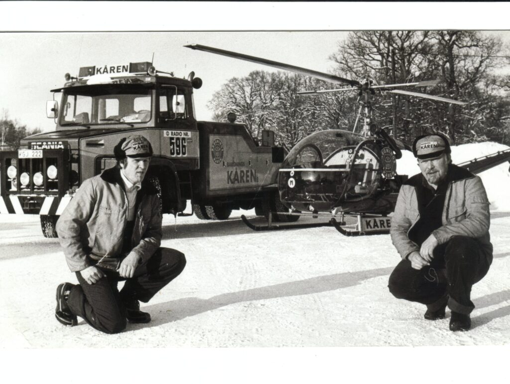 Blomman och Janne framför helikopter och tungbil.